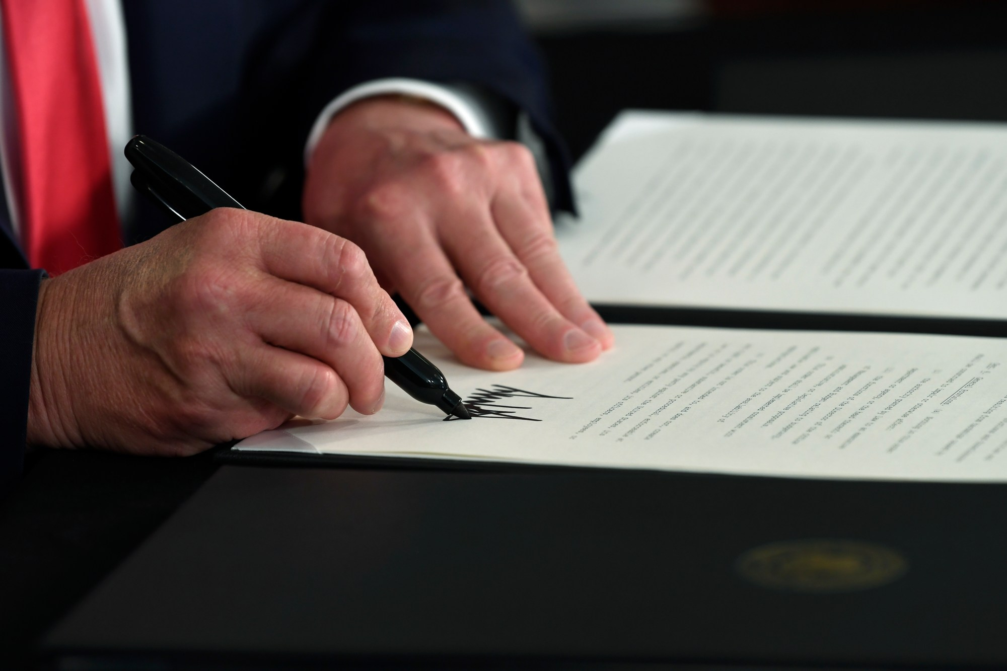 Donald Trump signs an executive order during a news conference at the Trump National Golf Club in Bedminster, N.J., Saturday, Aug. 8, 2020. (AP Photo/Susan Walsh)