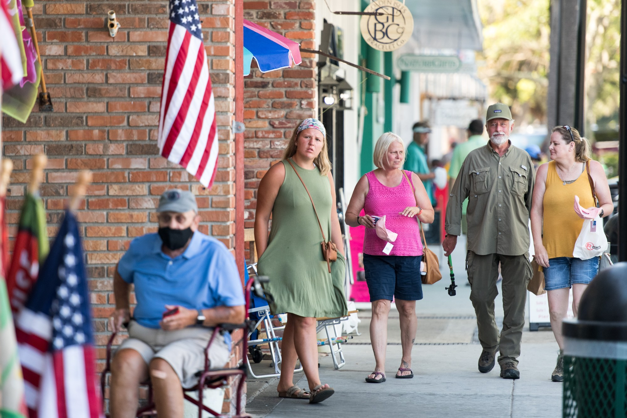 People walk down the sidewalk on July 17, 2020, in St. Simons Island, Georgia. Georgia Gov. Brian Kemp made an order earlier in the week that forbade municipal officials from setting mandatory face-covering policies. (Sean Rayford/Getty Images)