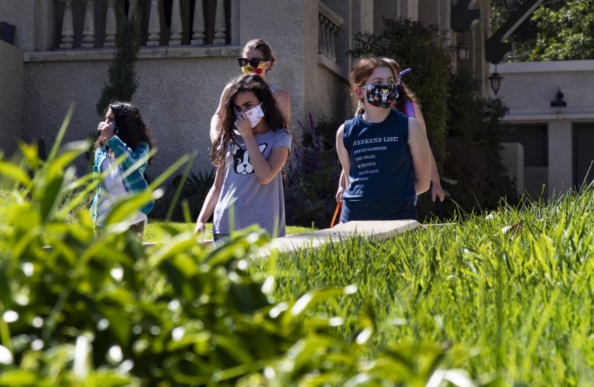Wearing masks for protection, Rosie Roth, left, Penelope Roth and Ellie Bristow walk to a cooking class during home school in the midst of the coronavirus pandemic in Riverside. (Gina Ferazzi / Los Angeles Times)