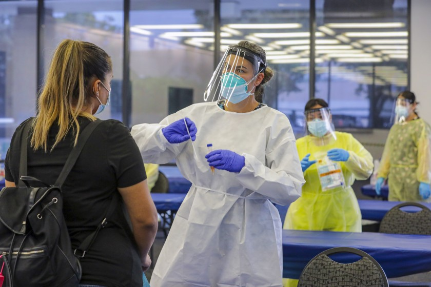 Elizabeth McKinnon explains to Glenda Guerra how to self-swab for a COVID-19 test at the Ontario Convention Center on July 24, 2020. (Irfan Khan / Los Angeles Times)