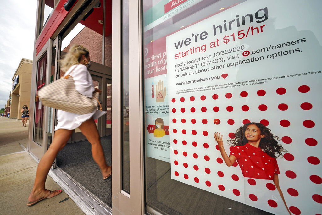 In this Sept. 2, 2020, file photo, a help wanted sign hangs on the door of a Target store in Uniontown, Pa. Hundreds of thousands of Americans likely applied for unemployment benefits last week, a high level of job insecurity that reflects economic damage from the coronavirus outbreak. (AP Photo/Gene J. Puskar, File)