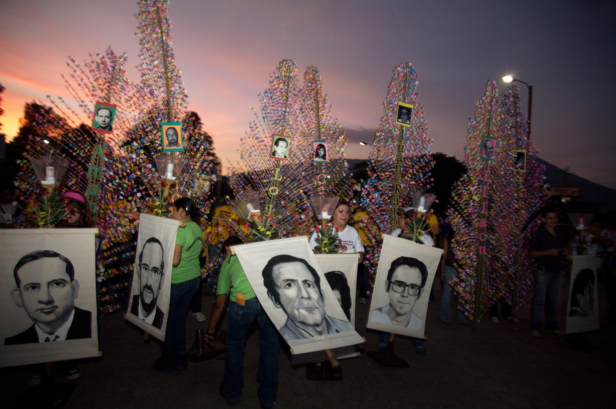 In this Nov. 15, 2008 file photo, people hold banners depicting six Jesuit priests massacred in 1989, during a memorial to mark the 19th anniversary of their death, in San Salvador. For years, attempts within El Salvador to investigate and prosecute the masterminds of the massacre during that country's civil war have been delayed and deflected by legal maneuvers. (Edgar Romero/AP Photo File)