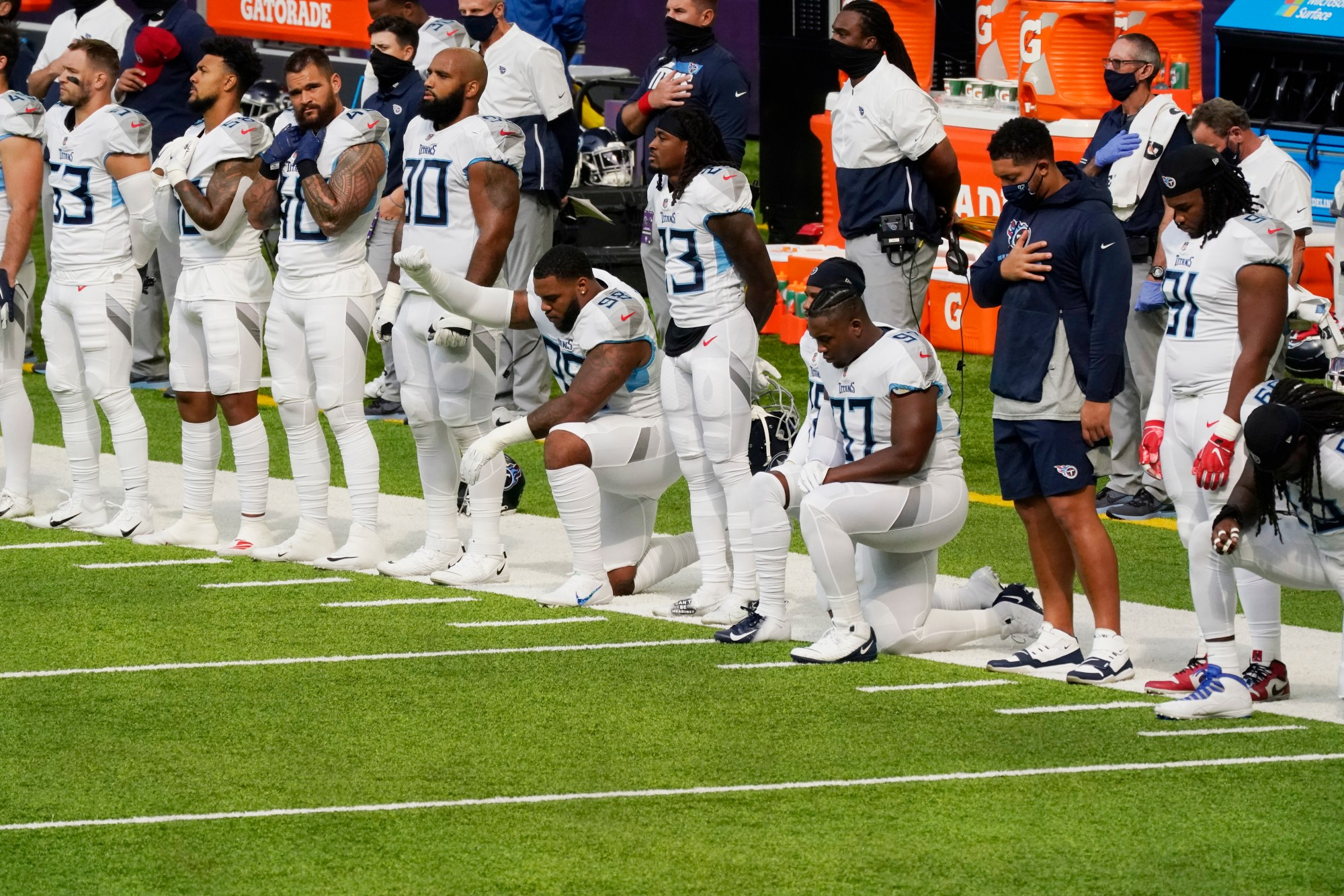 Members of the Tennessee Titans take part in the national anthem before an NFL football game against the Minnesota Vikings, Sunday, Sept. 27, 2020, in Minneapolis. The NFL says the Tennessee Titans and Minnesota Vikings are suspending in-person activities after the Titans had three players test positive for the coronavirus, along with five other personnel. The league says both clubs are working closely with the NFL and the players' union on tracing contacts, more testing and monitoring developments. The Titans are scheduled to host the Pittsburgh Steelers on Sunday.(AP Photo/Jim Mone)