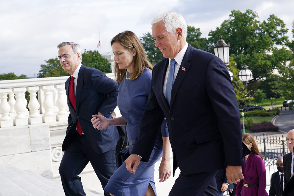 Judge Amy Coney Barrett, President Donald Trump's nominee for the U.S. Supreme Court, is escorted to the Senate by Vice President Mike Pence, right, where she will begin a series of meetings to prepare for her confirmation hearing, at the Capitol in Washington, Tuesday, Sept. 29, 2020. (AP Photo/Susan Walsh, POOL)