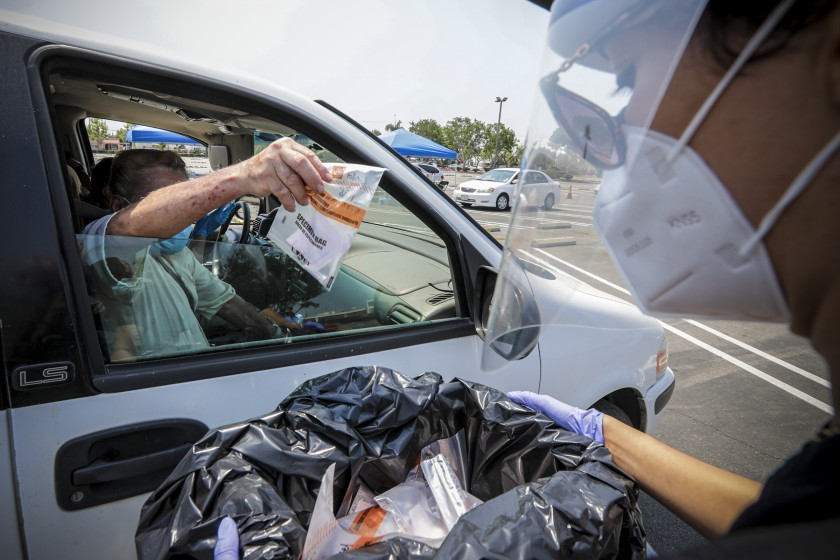 Daniel Mendoza drops off a sample at a drive-in COVID-19 testing site in a Santa Ana College parking lot on Aug. 22, 2020. (Irfan Khan / Los Angeles Times)