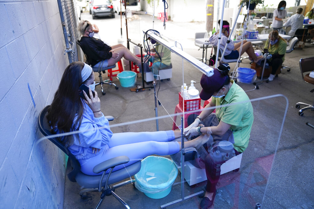 Madeline Witt, left, gets a pedicure outside Pampered Hands nail salon on July 22, 2020, in Los Angeles. (AP Photo/Ashley Landis)