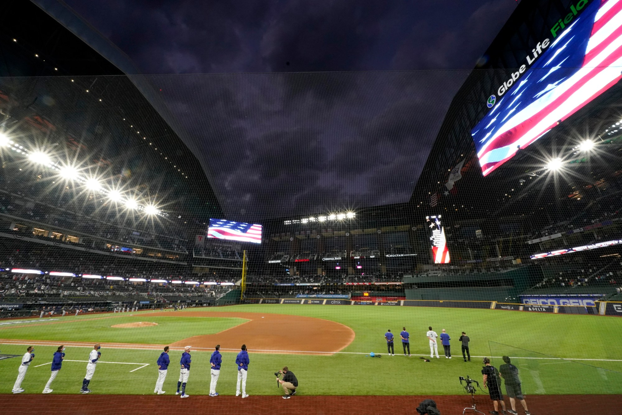 Members of the Los Angeles Dodgers stand during the national anthem before Game 7 of a baseball National League Championship Series Sunday, Oct. 18, 2020, in Arlington, Texas. (AP Photo/Eric Gay)