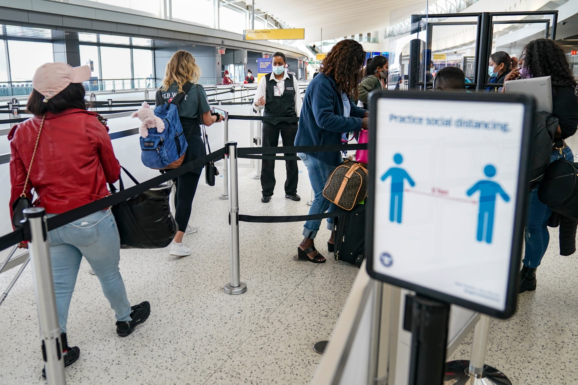 Transportation Security Administration personnel and travelers observe COVID-19 transmission prevention protocols at John F. Kennedy International Airport in New York on Oct. 20, 2020. (John Minchillo / Associated Press)