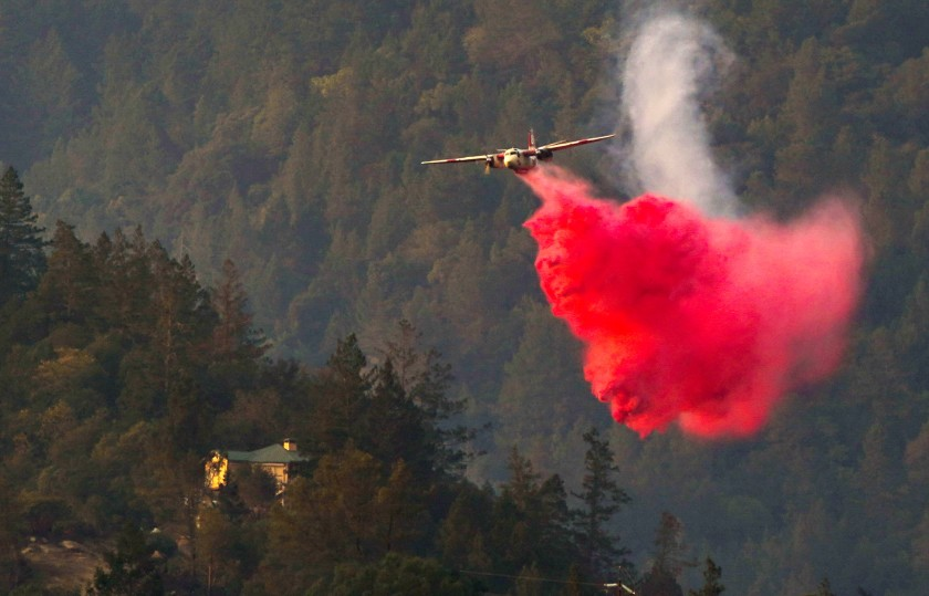 An aircraft drops fire retardant on the Glass fire in Napa County.(Kent Nishimura / Los Angeles Times)