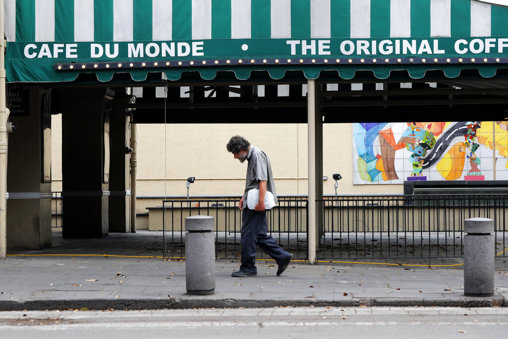 In this March 27, 2020, file photo, a man walks past the Cafe Du Monde restaurant, which was closed but has since reopened, in the French Quarter of New Orleans. (AP Photo/Gerald Herbert, File)