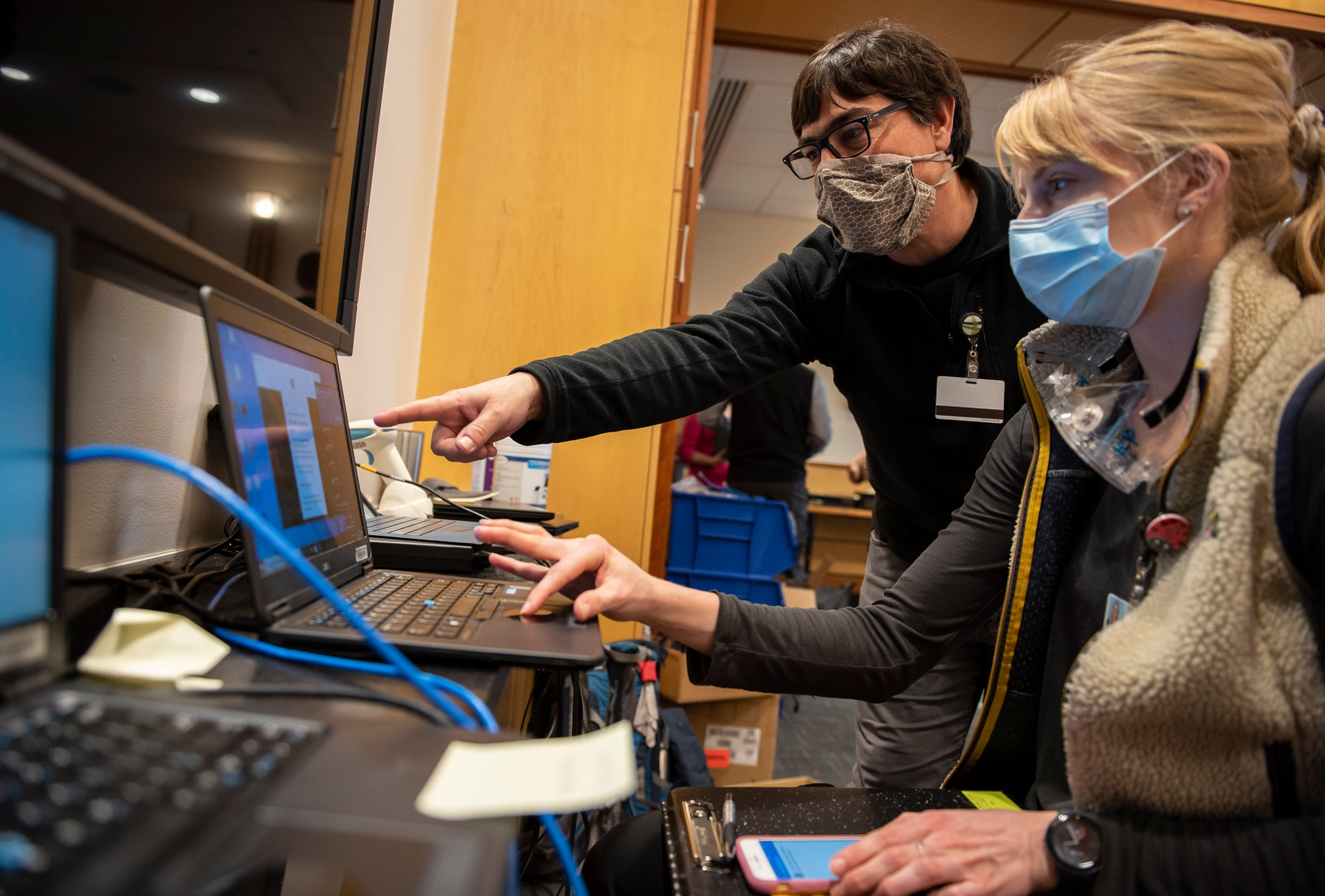 In this photo provided by the University of Vermont Health Network, IT staff help clinical providers set up new computers at the University of Vermont Medical Center in Burlington, Vt., on Friday, Nov. 20, 2020. (Ryan Mercer/University of Vermont Health Network via AP)