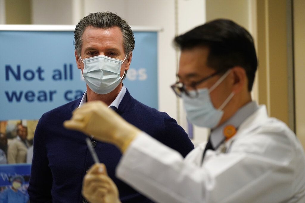 California Gov. Gavin Newsom watches as the Pfizer-BioNTech COVID-19 vaccine is prepared by Director of Inpatient Pharmacy David Cheng at Kaiser Permanente Los Angeles Medical Center on Dec. 14, 2020. (AP Photo/Jae C. Hong)