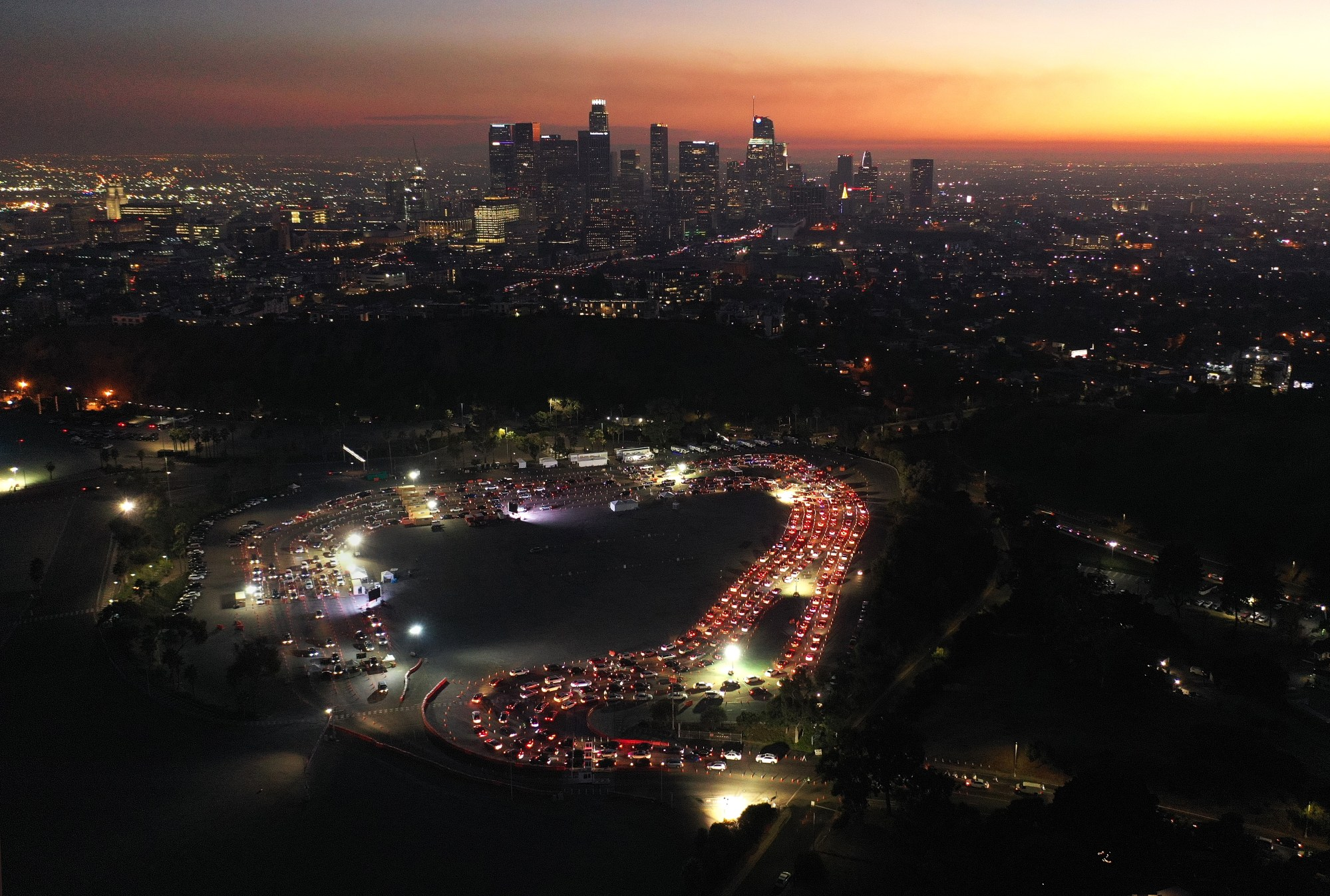 In an aerial view from a drone, cars are lined up at Dodger Stadium for COVID-19 testing as dusk falls over downtown Los Angeles on Dec. 2, 2020. (Mario Tama / Getty Images)
