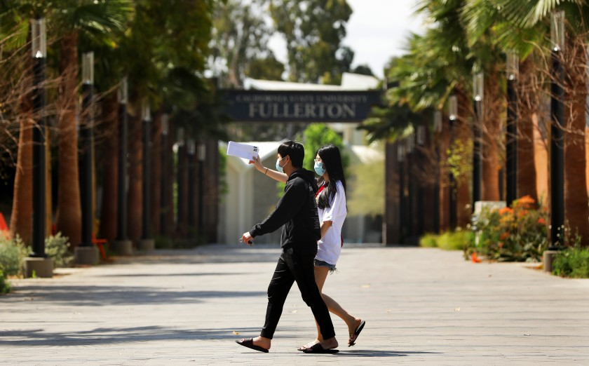 Two students wearing masks walk on the Cal State Fullerton campus in 2020. (Christina House / Los Angeles Times)