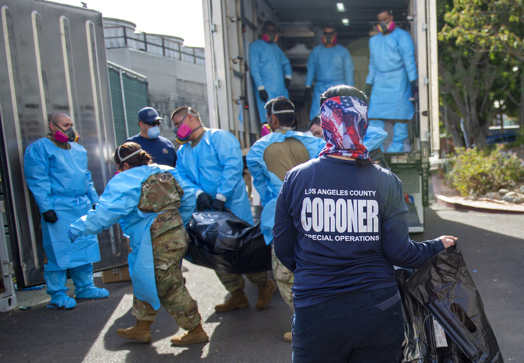 "In this Jan. 12, 2021, file photo, provided by the Los Angeles County Department of Medical Examiner-Coroner, Elizabeth ""Liz"" Napoles, right, works alongside with National Guardsmen who are helping to process the COVID-19 decedents to be placed into temporary storage at the coroner's office in Los Angeles. (via Associated Press)"