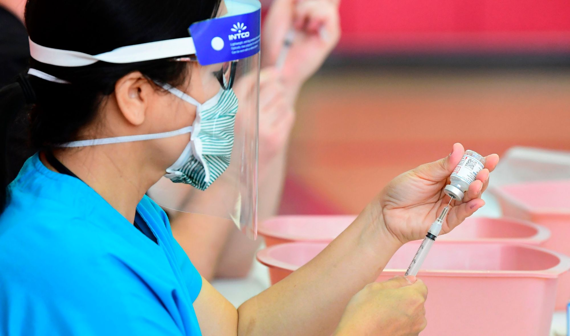 Registered nurses transfer the Moderna COVID-19 vaccine from a bottle into a syringe ready for vaccination at the Corona High School gymnasium in the Riverside County city of Corona, on Jan. 15, 2021. (FREDERIC J. BROWN/AFP via Getty Images)