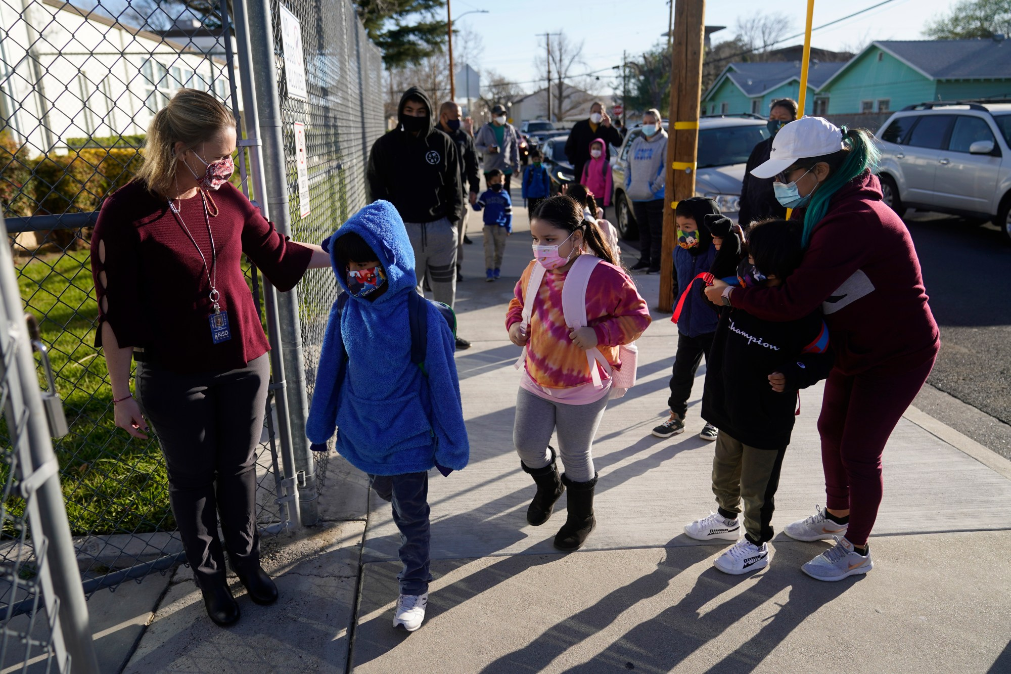 Assistant Principal Janette Van Gelderen, left, welcomes students at Newhall Elementary School in Santa Clarita on Feb. 25, 2021. Elementary school students returned to school this week in the Newhall School District. (Marcio Jose Sanchez / Associated Press)