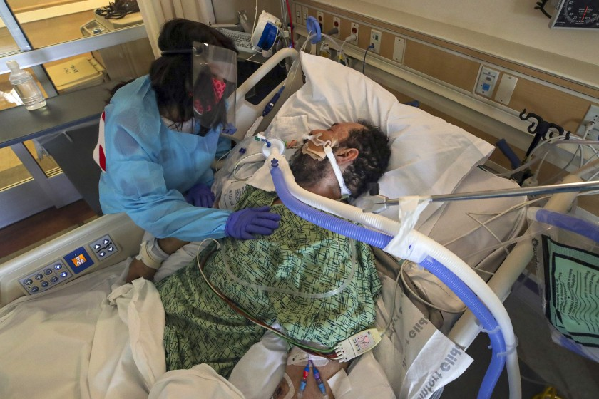 Patty Trejo, left, visits her husband, Joseph Trejo, a 53-year-old locksmith with the Anaheim Union High School District and a COVID-19 patient on a ventilator, in the ICU at St. Jude Medical Center in Fullerton on Feb. 15.(Irfan Khan/Los Angeles Times)