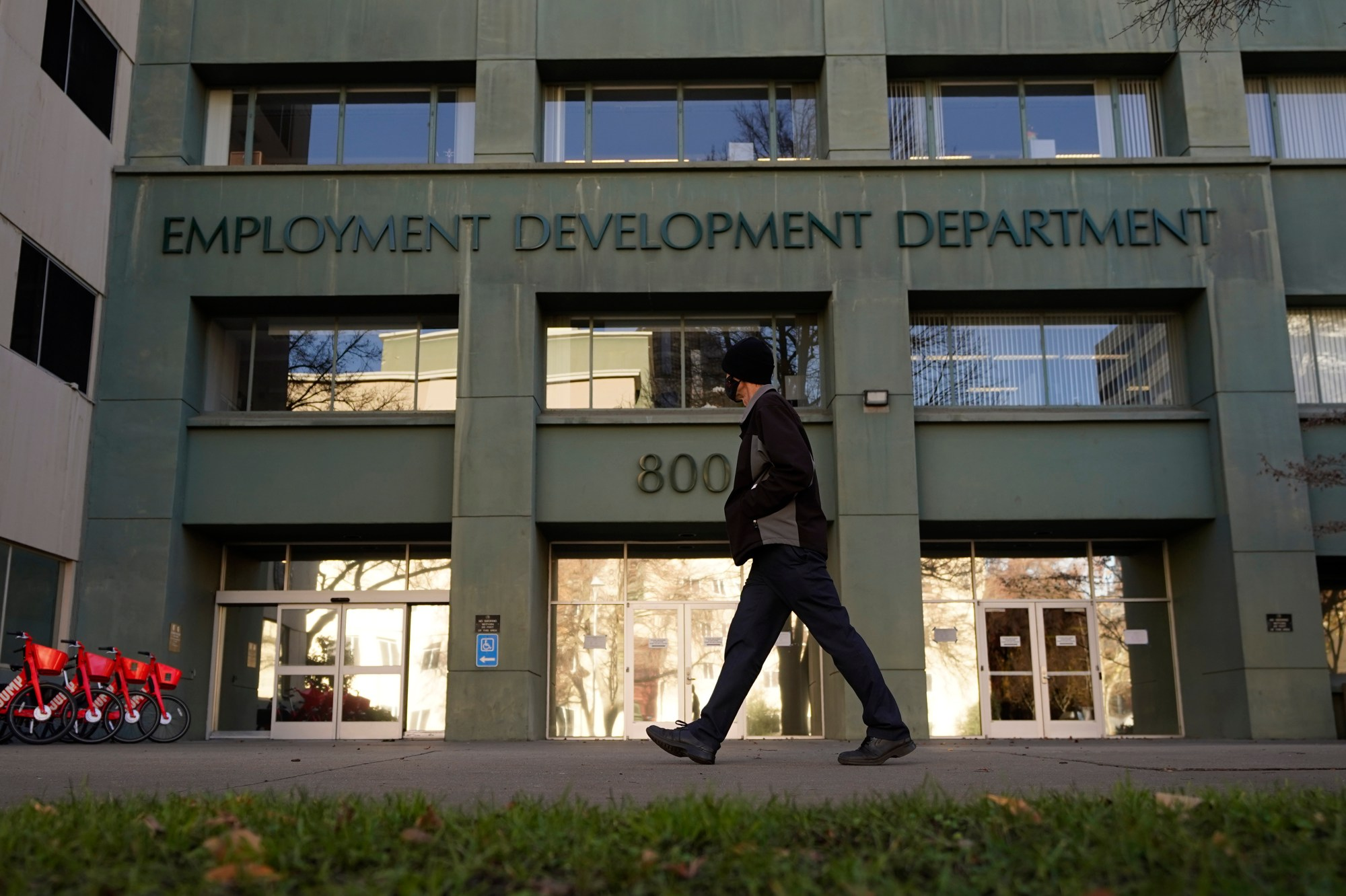 In this Dec. 18, 2020, file photo, a person passes the office of the California Employment Development Department in Sacramento, Calif. On Wednesday, Feb. 3, 2021.(AP Photo/Rich Pedroncelli, File)