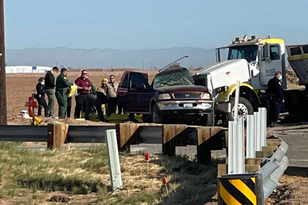 Authorities work at the scene of a deadly crash involving a semitruck and an SUV in Holtville, near the California border with Mexico, on March 2, 2021. (KYMA via Associated Press)