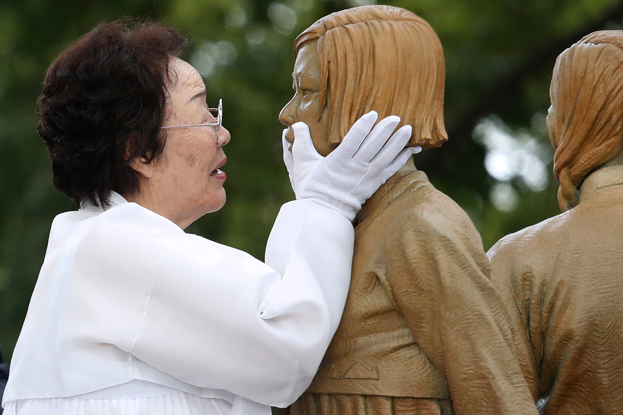 "In this Aug. 14, 2019, file photo, Lee Yong-soo, who was forced to serve for the Japanese troops as a sex slave during World War II, touches the face of a statue of a girl symbolizing the issue of wartime ""comfort women"" during its unveiling ceremony in Seoul, South Korea. (AP Photo/Ahn Young-joon, File)"