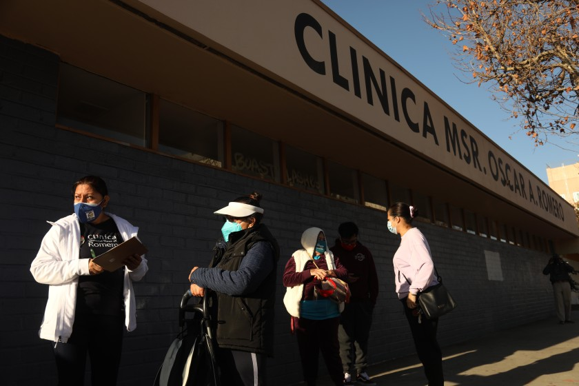 A staff member of Clinica Romero registers patients at a COVID-19 vaccination clinic.(Genaro Molina / Los Angeles Times)