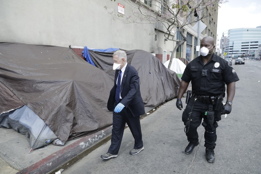 The proposed deal in L.A. is modeled after one put into place in Orange County by Judge David. O Carter, pictured in an undated photo touring skid row. (Myung J. Chun / Los Angeles Times)