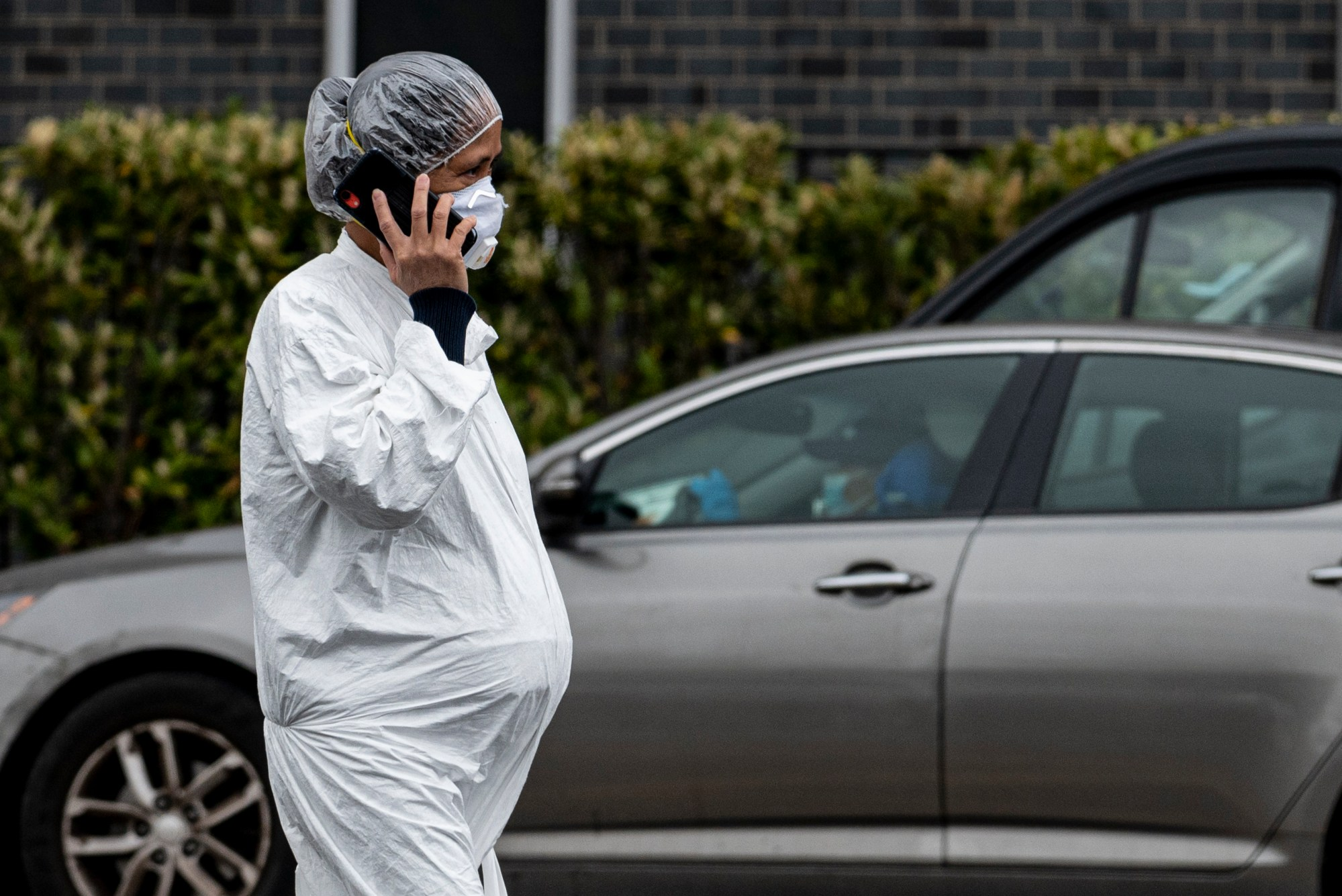 A pregnant woman wearing a hazmat suit and a mask walks in the streets in the Elmhurst neighbourhood of Queens on April 27, 2020 in New York City. (Johannes EISELE / AFP) (Photo by JOHANNES EISELE/AFP via Getty Images)