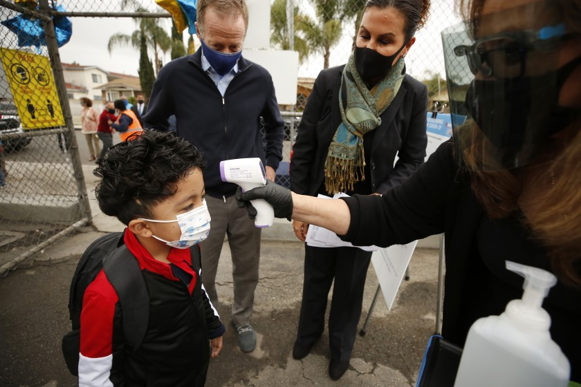 Kindergartener Jesus Mendez has his temperature taken Tuesday morning at Heliotrope Avenue Elementary as administrators look on.(Al Seib / Los Angeles Times)