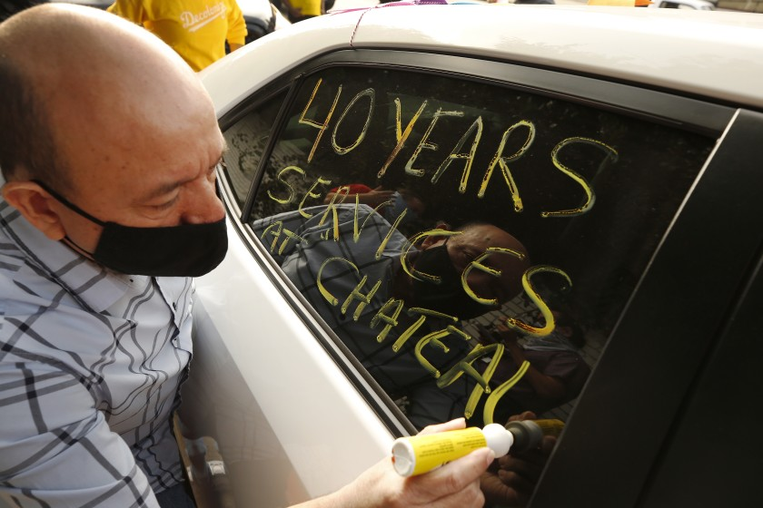 Carlos Barrera, who worked in valet parking for 40 years at the Chateau Marmont, writes messages on the window of his car in support of workers who lost their jobs at the Chateau Marmont as they form a caravan to travel from the L.A. area to Sacramento to protest in favor of a bill that would protect their jobs. (Al Seib/Los Angeles Times)