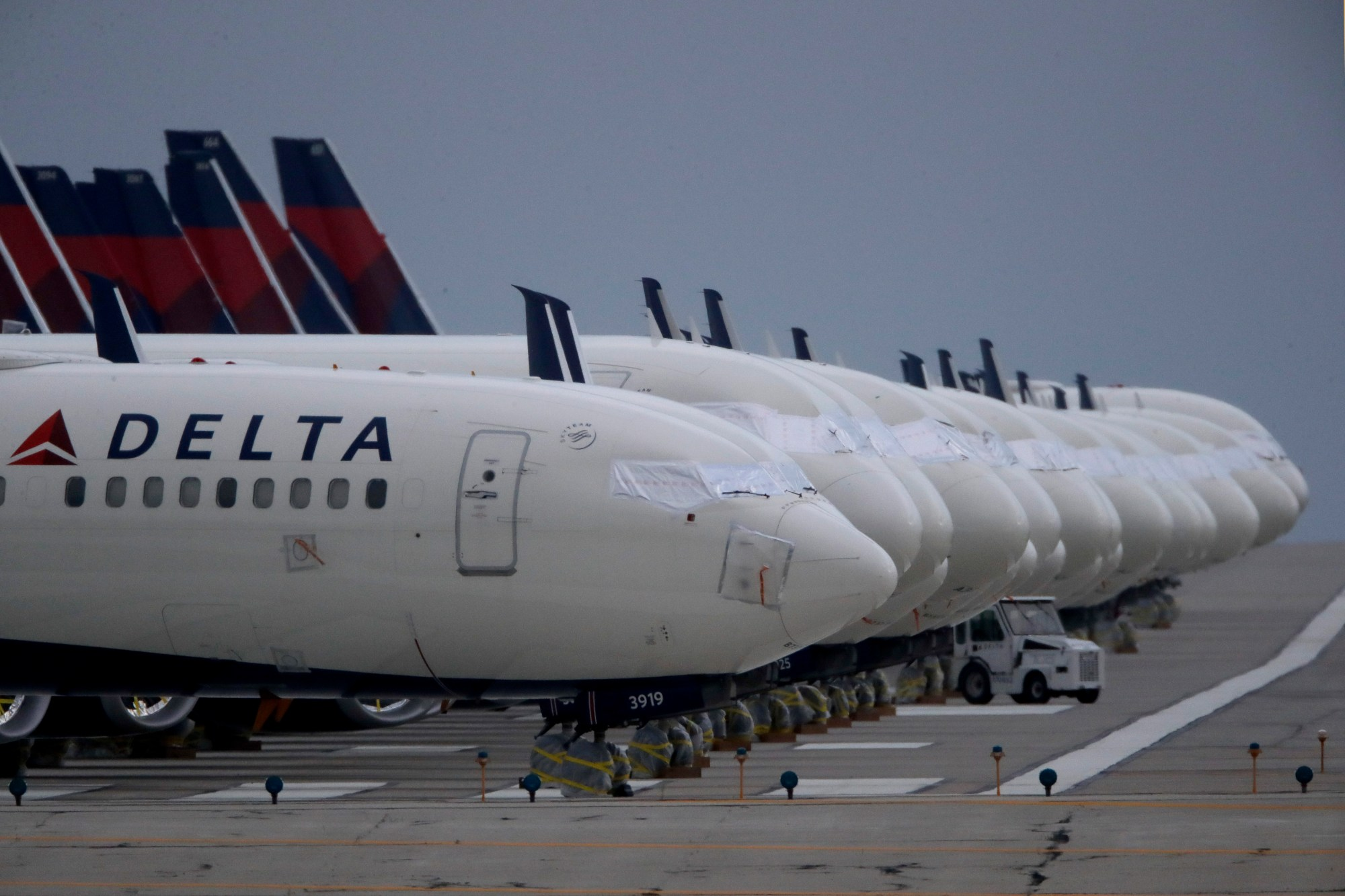 In this May 14, 2020 file photo, several dozen mothballed Delta Air Lines jets are parked on a closed runway at Kansas City International Airport in Kansas City, Mo. (AP Photo/Charlie Riedel, File)