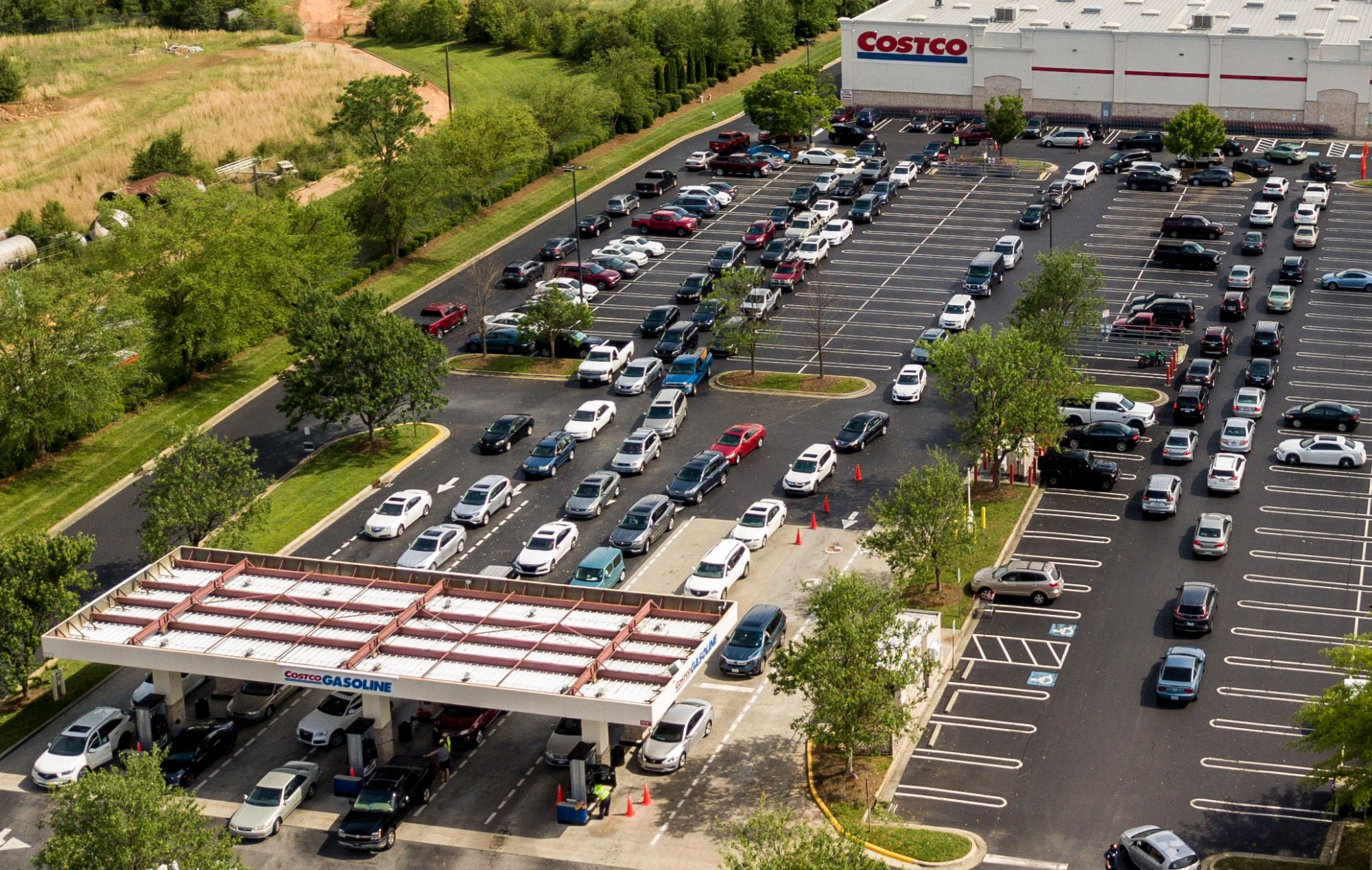In this aerial image taken with a drone, numerous vehicles line up for gasoline at Costco on Wendover Avenue in Greensboro, N.C., on Tuesday, May 11, 2021. As the shutdown of a major fuel pipeline entered into its fifth day, efforts are under way to stave off potential fuel shortages, though no widespread disruptions were evident. The Colonial Pipeline, which delivers about 45% of the fuel consumed on the East Coast, was hit by a cyberattack on Friday. (Woody Marshall/News & Record via AP)