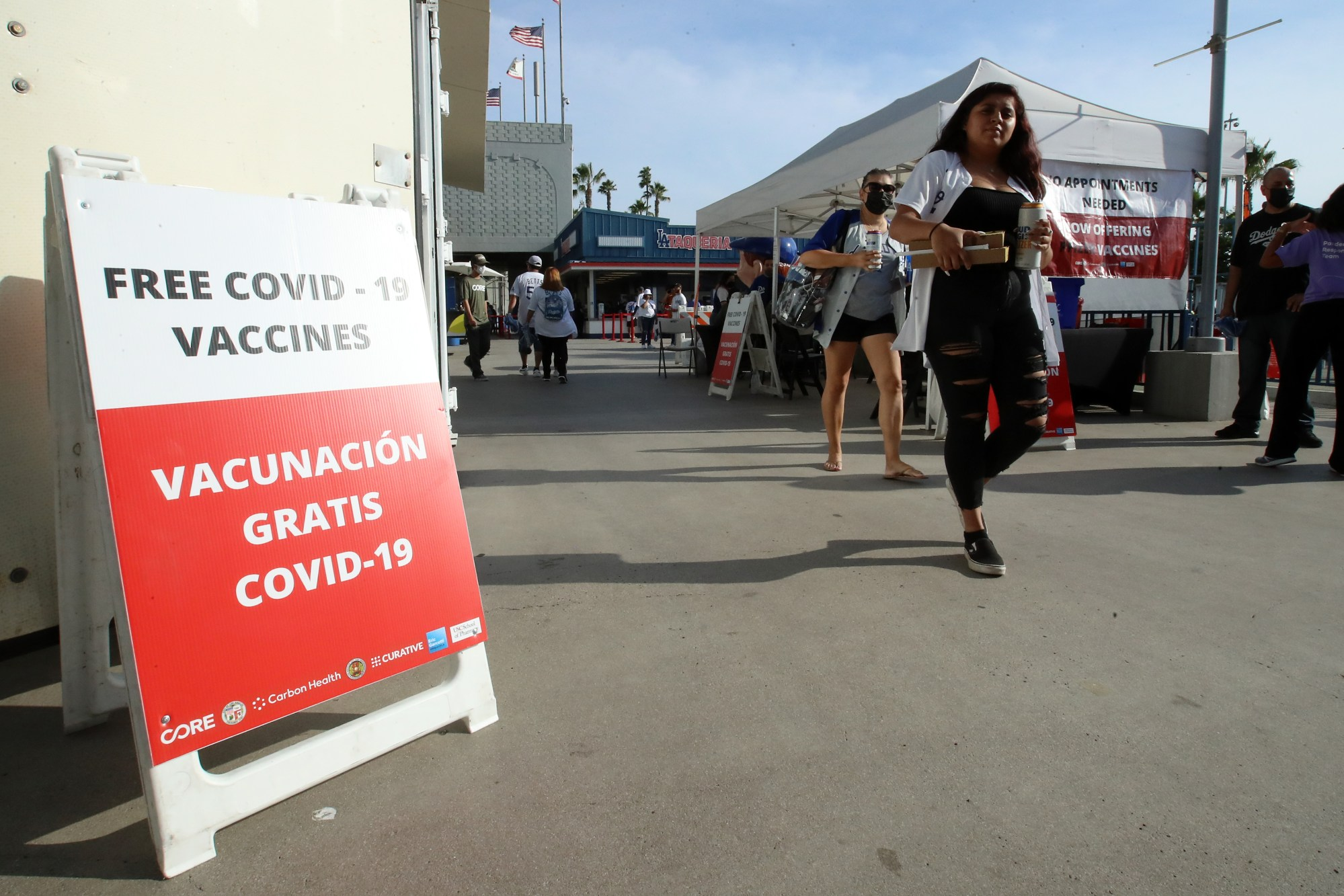 Fans walk past a COVID-19 vaccination tent before the game between the Los Angeles Dodgers and the San Francisco Giants at Dodger Stadium on July 22, 2021. (Katelyn Mulcahy/Getty Images)