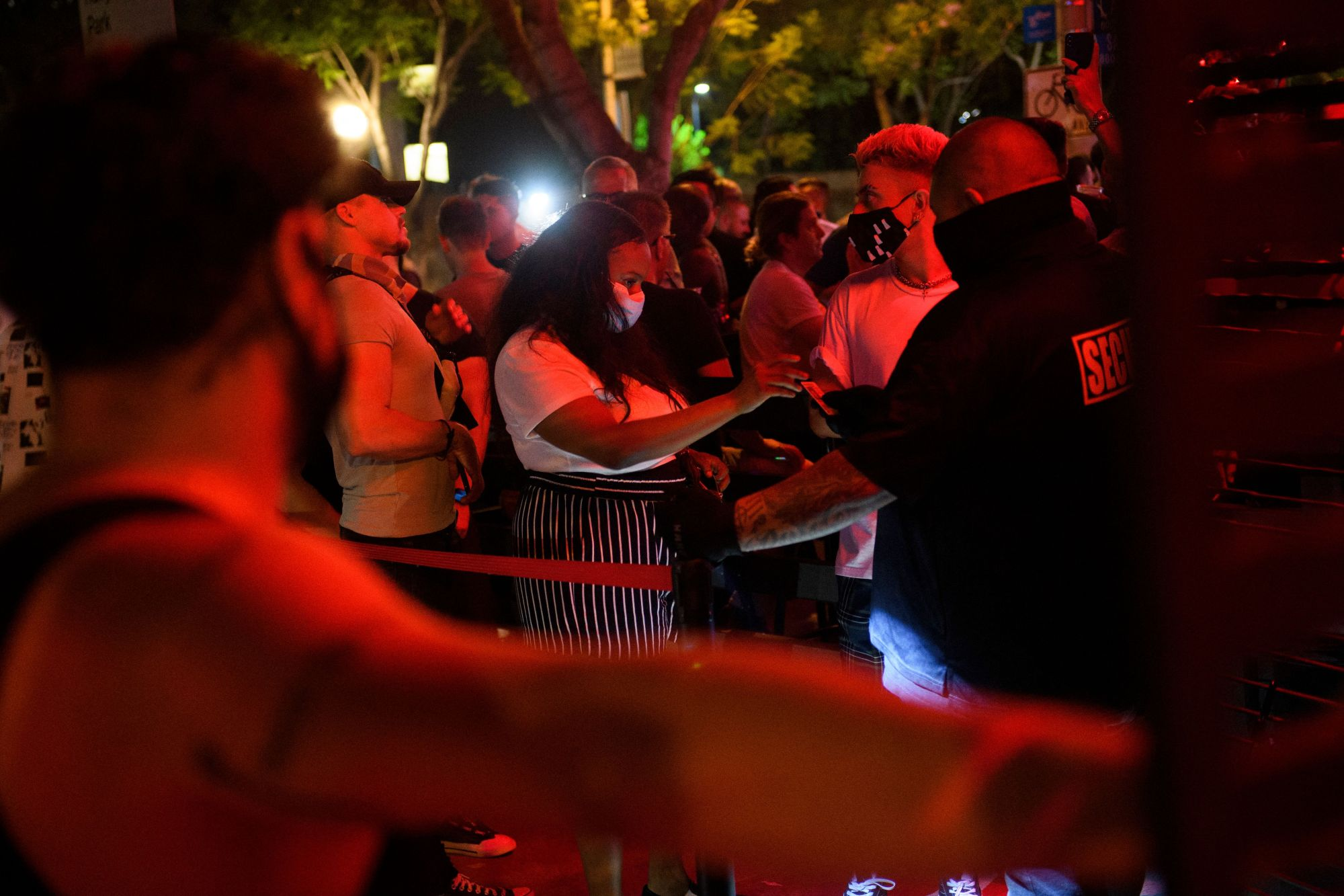 Customers are required by security to wear face masks to enter a bar in West Hollywood on July 18, 2021. (Patrick T. Fallon / AFP / Getty Images)