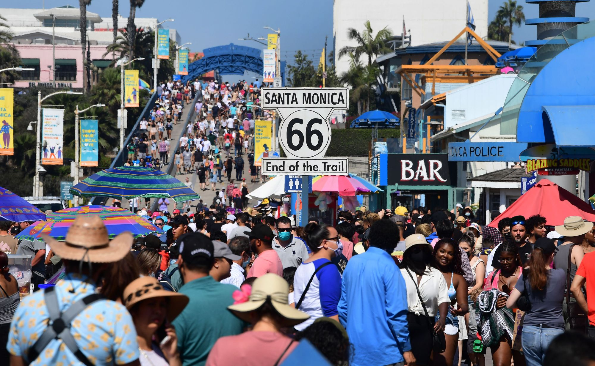 A crowd of people makes it's way to the end of the trail of Route 66 at Santa Monica Pier as people take to the coastline to beat the heat on Sept. 5, 2021. (FREDERIC J. BROWN/AFP via Getty Images)