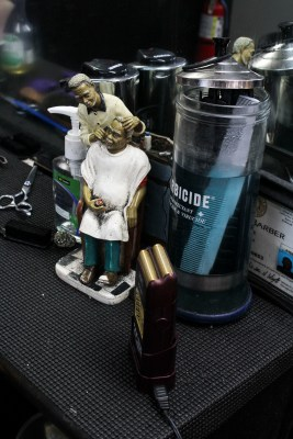 """A figurine sits on the shelf in front of Danny Head's chair as he sweeps hair after finishing up with a client. Head is one of the Master Barbers of one of the All-star Barbershop locations in San Marcos, which is on South LBJ. """"Cutting hair is an art,"""" Head said. """"Not an art as in getting a nice tapered-fade, but as in talking to somebody, sitting them in your chair and giving them advice."""" Head has been working at All-star Barbershop for about four years. Photo by DaLyah Jones."""