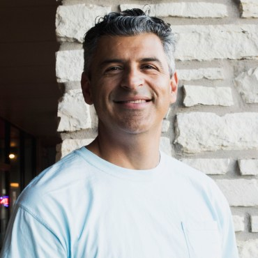 A head shot of Hays county judge Democratic candidate Ruben Becerra against a stone wall.