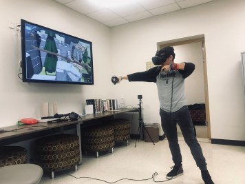 student using HTC goggles to play archery game