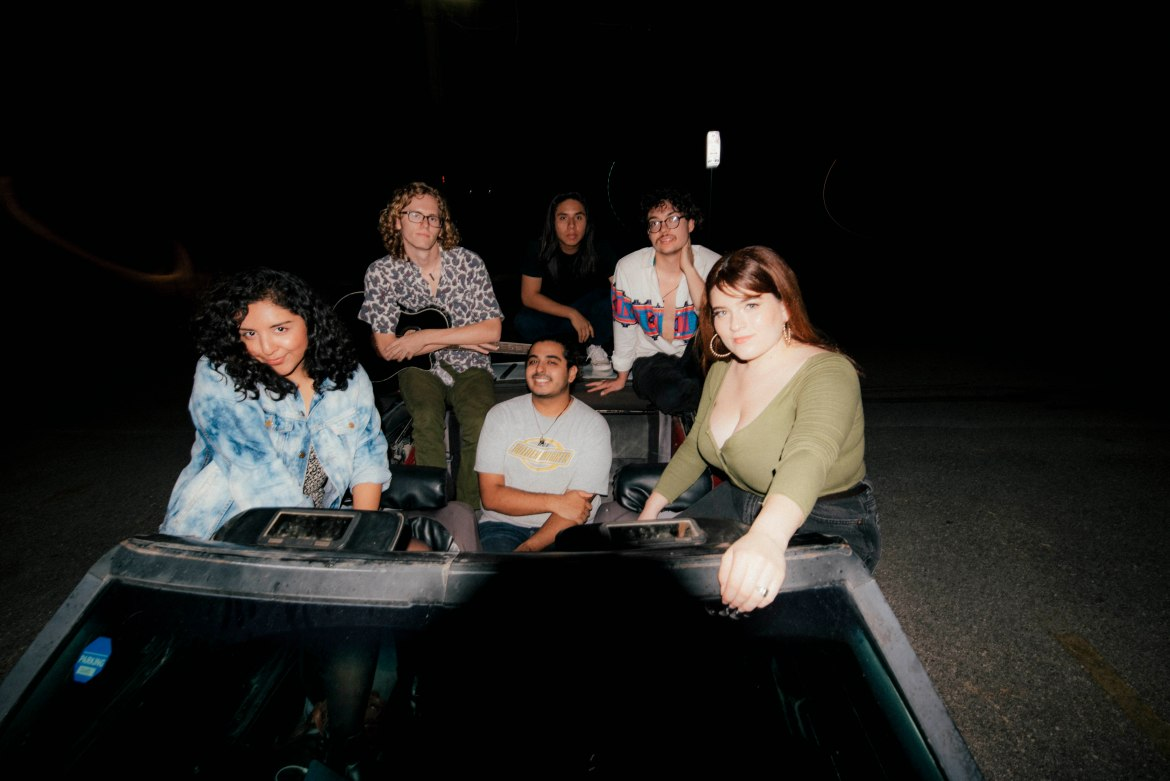 Four of the five members of Wezmer along with two from their team pose in the dark sitting on top of the seats of a convertible car with the roof off. They are exposed by flash only and the photo is taken from in front of the car.