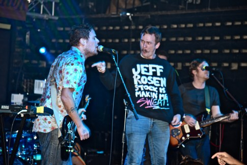 """A fan who crowd surfed his way onstage, pointing at Rosenstock and wearing a sweatshirt that says """"Jeff Rosenstock is making me sweat!"""""""