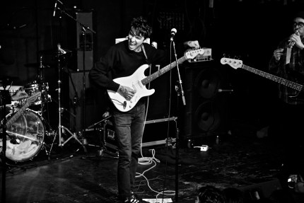 Black and white photo of Joyce Manor's frontman Barry Johnson tuning his guitar onstage.
