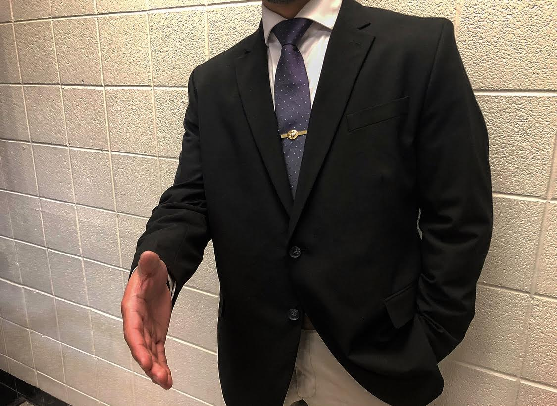 A well dressed individual extending his hand for a shake