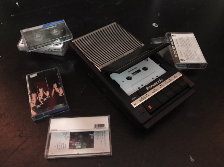 A cassette player that is surrounded by multiple cassette tapes.