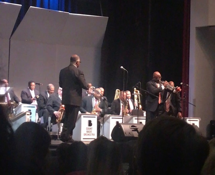 Member of the count basie orchestra performing a trumpet solo on stage