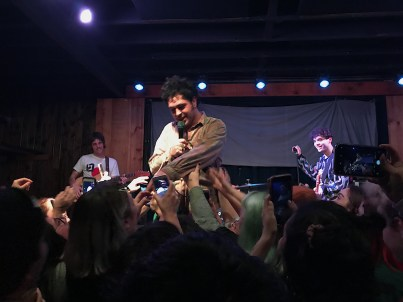 Left to right, there is the guitarist, lead singer, bassest, and the drummer in the back. The audience's hands are reaching towards the lead singer.