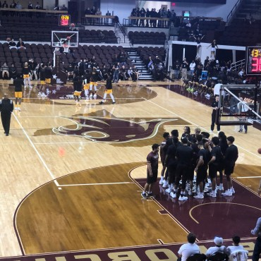 Many basketball players huddling before the start of the game.