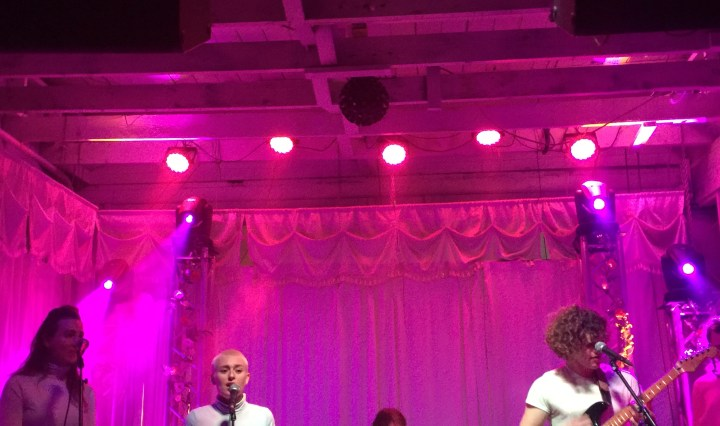 A band lined up on the stage with pink lights. Two women are singing.