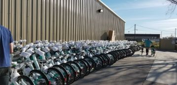 A row of bikes lined up alongside the Veoride warehouse. Bikes are covered in shipping packaging.