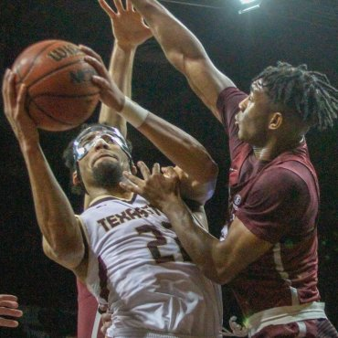 Basketball Player in white jersey goes up for a layup against another Basketball player in a maroon jersey.