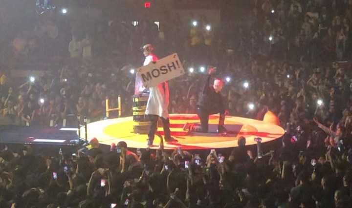"""Hype man holding up a sign that says """"mosh"""" with A$AP kneeling on the ground with his fist up"""